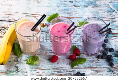 Fresh milk, raspberry, banana and blueberry drinks on wooden table, assorted protein cocktails with fresh fruits. Natural background.  - stock photo