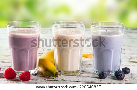 Fresh milk, raspberry, blueberry and banana drinks on wooden table, assorted protein cocktails with fresh fruits and nature background. Healthy lifestyle.  - stock photo