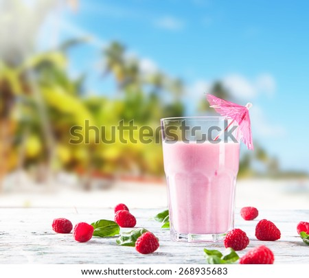 Fresh milk, raspberry drink on wooden table, assorted protein cocktails with fresh fruits. Tropical beach background. - stock photo