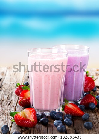 Fresh milk, strawberry and blueberry drinks on wodeen table, assorted protein cocktails with fresh fruits. Summer drinks on the beach and blue sky. - stock photo