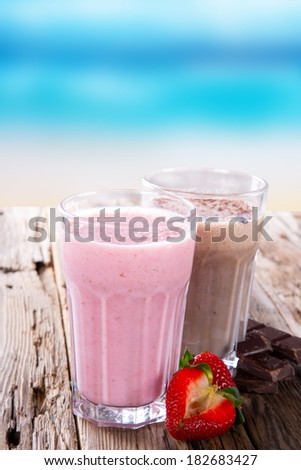 Fresh milk, strawberry and chocolate drinks on wodeen table, assorted protein cocktails with fresh fruits. Summer drinks on the beach with blue sky. - stock photo