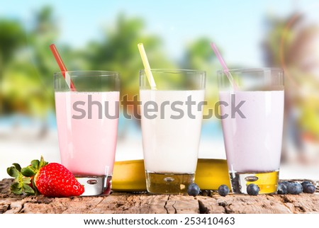 Fresh milk, strawberry, blueberry  and banana drinks on wooden table, assorted protein cocktails with fresh fruits and tropical beach background. - stock photo