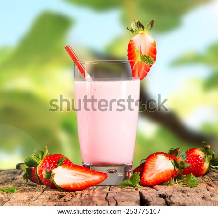 Fresh milk, strawberry drink on wooden table, assorted protein cocktail with fresh fruits and nature green background.  - stock photo