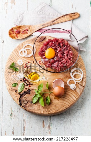Fresh minced meat with onion and spices in bowl on wooden cutting board on blue background - stock photo
