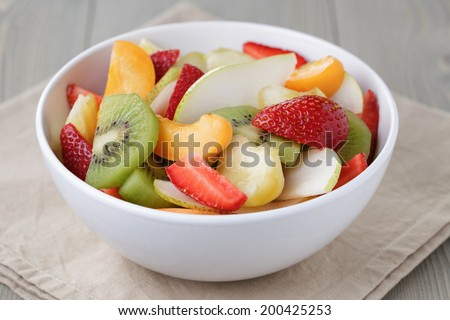 fresh mix fruit salad with strawberry, kiwi and peach, on wood table - stock photo