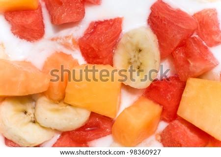 Fresh mixed fruit salad with banana, papaya,watermelon in milk - stock photo