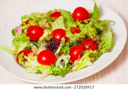 fresh mixed salad leaves with cherry tomatoes - stock photo