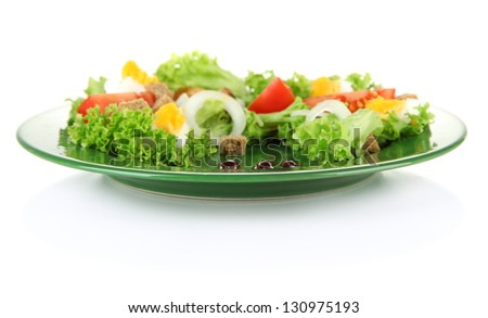 Fresh mixed salad with eggs, tomato, salad leaves and other vegetables on color plate, isolated on white - stock photo