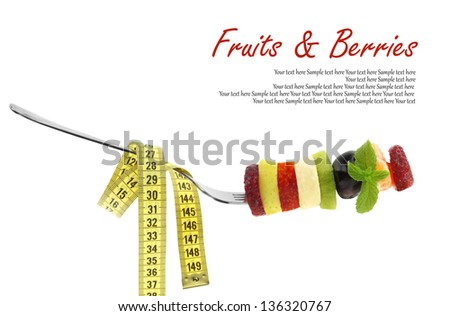 Fresh mixed slices of fruits on a fork with measuring tape - stock photo