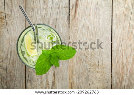 Fresh mojito cocktail on wooden table with copy space - stock photo