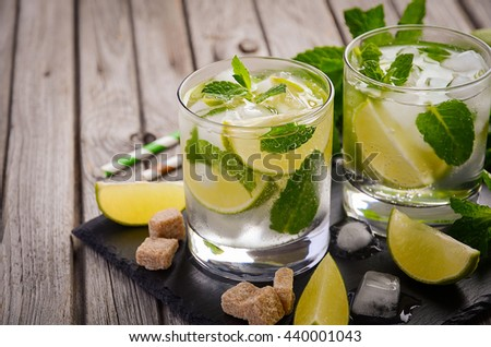Fresh mojito cocktail with lime and mint on rustic wooden background, selective focus, copy space - stock photo