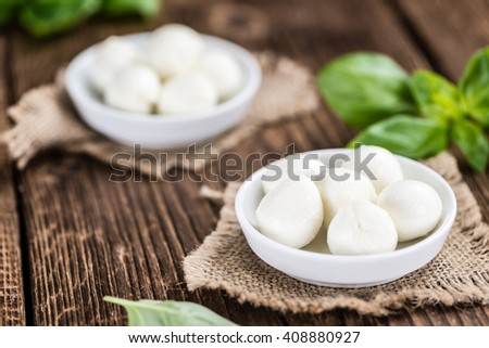 Fresh Mozzarella (close-up shot) on wooden background (selective focus) - stock photo