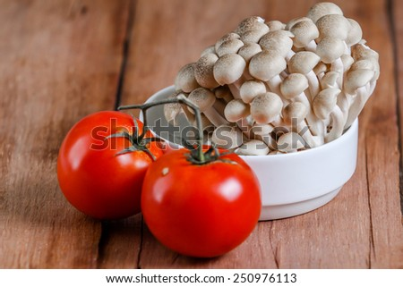 fresh mushroom with tomato on wooden table - stock photo