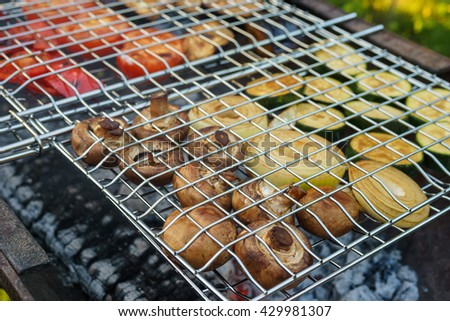 Fresh mushrooms and vegetables grilling in gridiron, picnic in summer outdoors - stock photo
