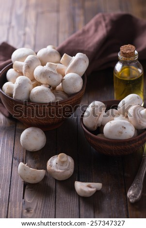 Fresh mushrooms in bowl on  wooden background. Selective focus.  - stock photo