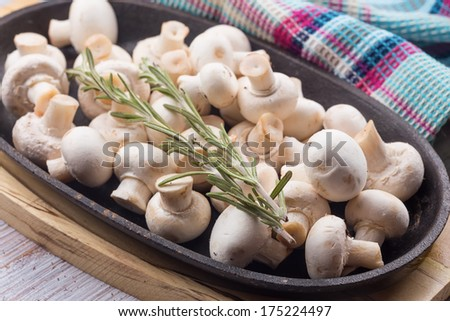 Fresh mushrooms in frying pan with rosemary. Selective focus. Rustic style. - stock photo