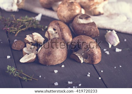 Fresh mushrooms with spices and herbs on a black board.Champignon mushrooms - stock photo