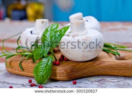 Fresh mushrooms with spices and herbs on old wooden board. - stock photo