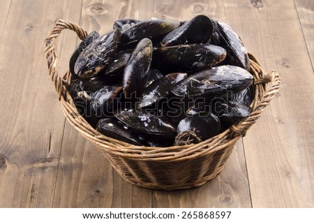 fresh mussel in a wicker basket on brown wooden table - stock photo