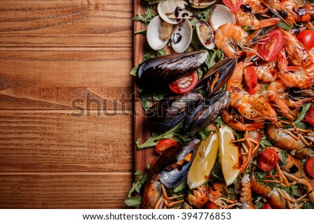 Fresh mussels, crayfish, shrimp decorated with arugula, tomatoes, lemon and sauce on a wooden board. Seafood platter - stock photo