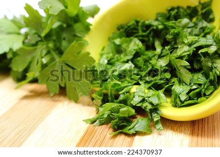 Fresh, natural, green chopped parsley in yellow dish and bunch of parsley in background lying on wooden cutting board, concept for healthy eating - stock photo