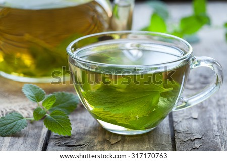 Fresh natural green melissa herbal tea in glass cup. Organic aromatherapy relaxation medical healthy beverage. Rustic wooden table background. Rustic style natural light. - stock photo