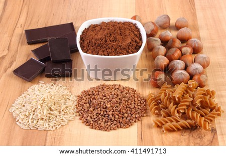 Fresh, natural ingredients and products containing magnesium and dietary fiber, healthy food and nutrition, wholemeal pasta, buckwheat, brown rice, hazelnut, cocoa, chocolate - stock photo