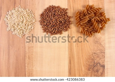Fresh, natural ingredients and products containing magnesium and dietary fiber, healthy food and nutrition, wholemeal pasta, buckwheat, brown rice, copy space for text - stock photo