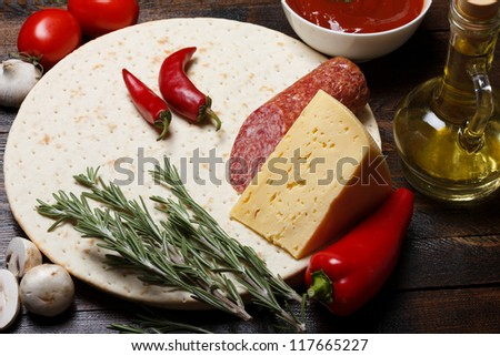 Fresh natural pizza ingredients on wooden table, ready for cooking - stock photo