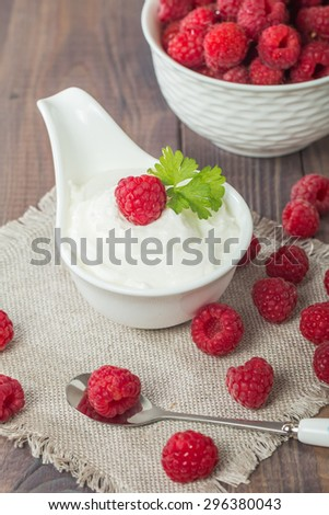fresh natural yogurt with raspberries in white bowl on wooden background - stock photo