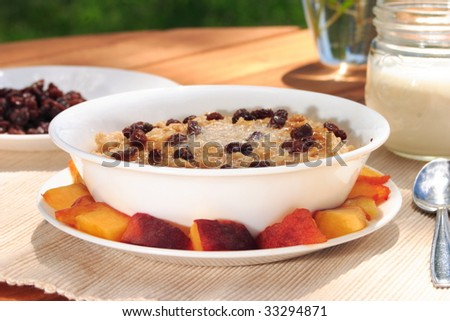 Fresh oatmeal topped with raisins, melted butter, and brown sugar. - stock photo