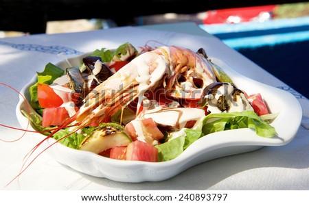 Fresh octopus salad with tomatoes,  fresh food, italian food, sea food in plate, fresh tuna and octopus salad, greek kitchen, sea food with tomatoes, tuna, garlic and herbs - stock photo