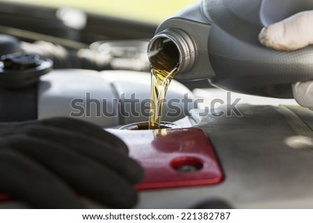 Fresh oil being poured into a car during a service - stock photo