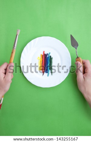 Fresh oil paint and painting instruments organized like a dish - stock photo