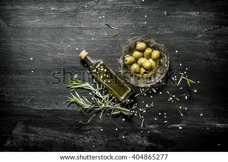 Fresh olives and the oil in the bottle with the rosemary. On black rustic background. - stock photo