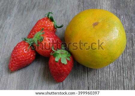 Fresh orange and strawberry isolated on table - stock photo
