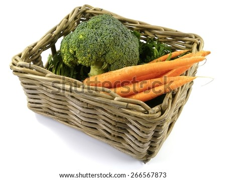 Fresh orange carrots with a green foliage and a green  broccoli in a basket over white - stock photo