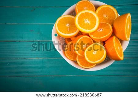 Fresh orange halves on rustic wooden kitchen table - stock photo