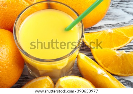 Fresh orange juice and ripe fruits on wooden table. - stock photo