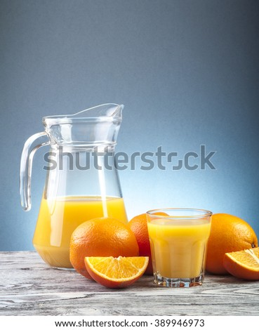 Fresh orange juice and ripe oranges on wooden table - stock photo
