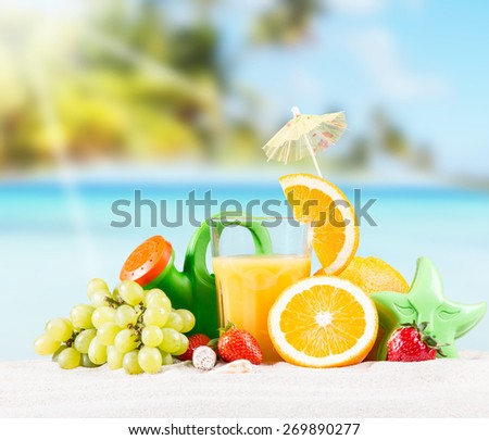 Fresh orange juice, fruits and children cake on sand with blue sky background, summer concept  - stock photo