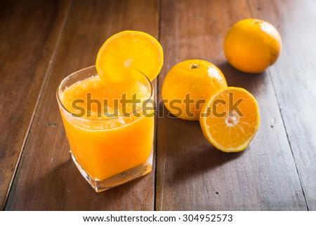 Fresh orange juice on wooden background - stock photo