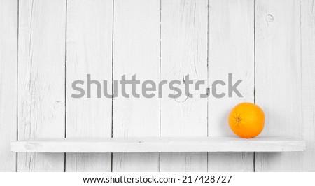 Fresh orange on wooden shelf. - stock photo