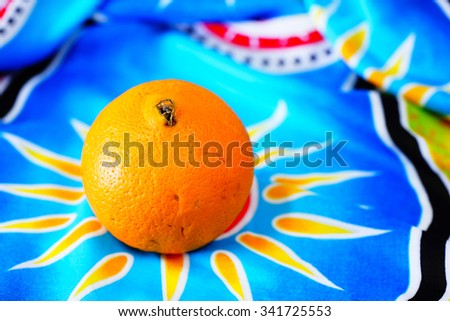 Fresh orange with colorful batik pattern cloth background:Close up,select focus with shallow depth of field. - stock photo