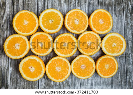 Fresh oranges cuted in half on a wooden background - stock photo