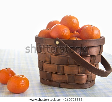 Fresh oranges in a basket on a picnic table - stock photo