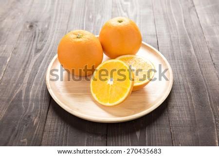 Fresh oranges on wooden dish, fresh fruits on wooden background - stock photo