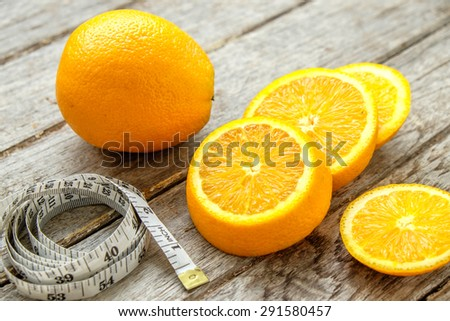 Fresh oranges sliced with measuring tape on wooden ,top view ,still life of fruit - stock photo