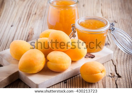 Fresh organic apricots on wooden board and homemade apricot chutney  in a glass jar - stock photo
