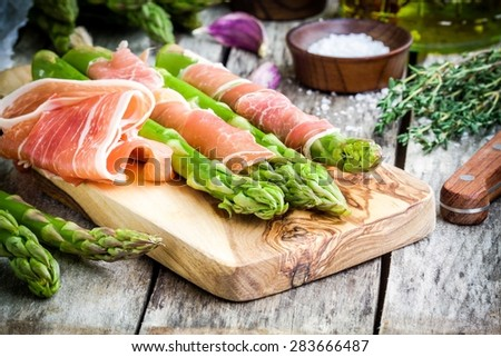 Fresh organic asparagus with prosciutto on a cutting board on rustic table - stock photo